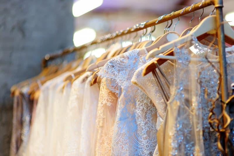 Немного красивых платьев свадьбы на вешалке стоковые изображения