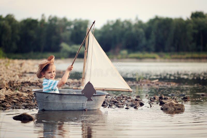 Немного 4 старого лет матроса мальчика на реке в рыбной ловле и плавании шлюпки стоковые фото