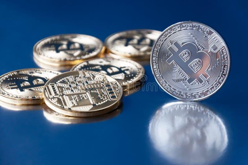 Немного bitcoin золота и серебряных монет лежит на голубом backgroundConcept секретной валюты стоковые фото
