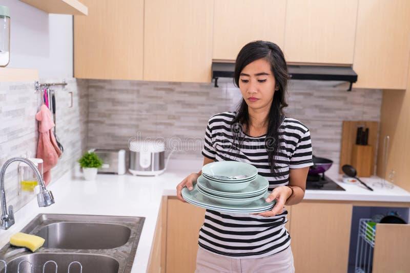 Ненависть женщины для того чтобы помыть блюдо стоковые фото