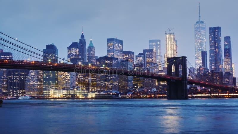 Ненастное Манхаттан и Бруклинский мост Верхние части небоскребов в облаках тонут Ночь приходит к делу стоковая фотография rf