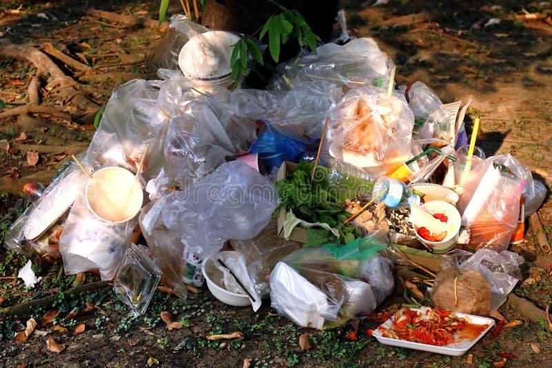Ненужная пластмасса, отброс, сброс, полиэтиленовые пакеты на основании дерева, ненужная загрязняя природа пищевых отходов старья  стоковые изображения