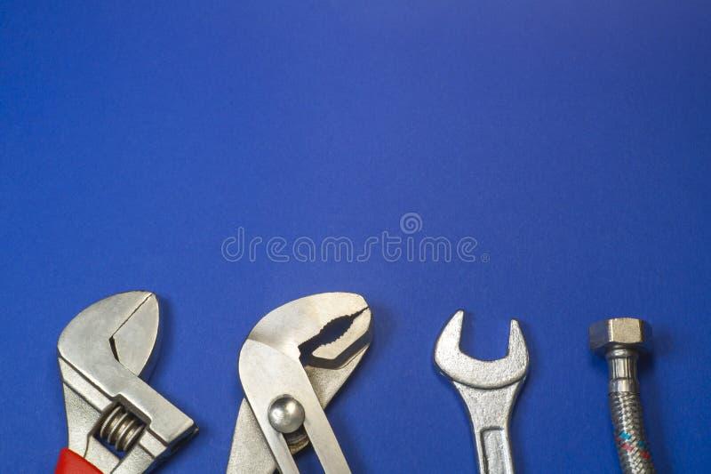 Необходимый набор инструментов для водопроводчиков на голубой предпосылке стоковое изображение rf