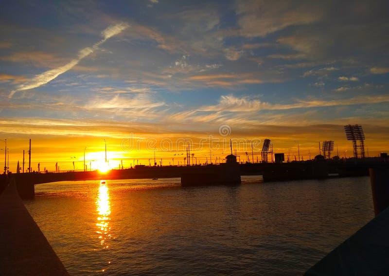Необыкновенный заход солнца за мостом стоковое фото