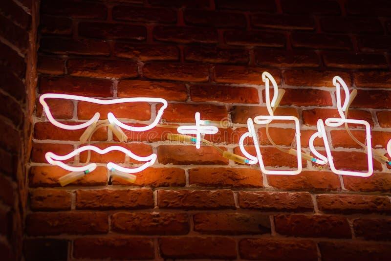 Неоновая вывеска с чашками кофе на предпосылке красной кирпичной стены стоковая фотография