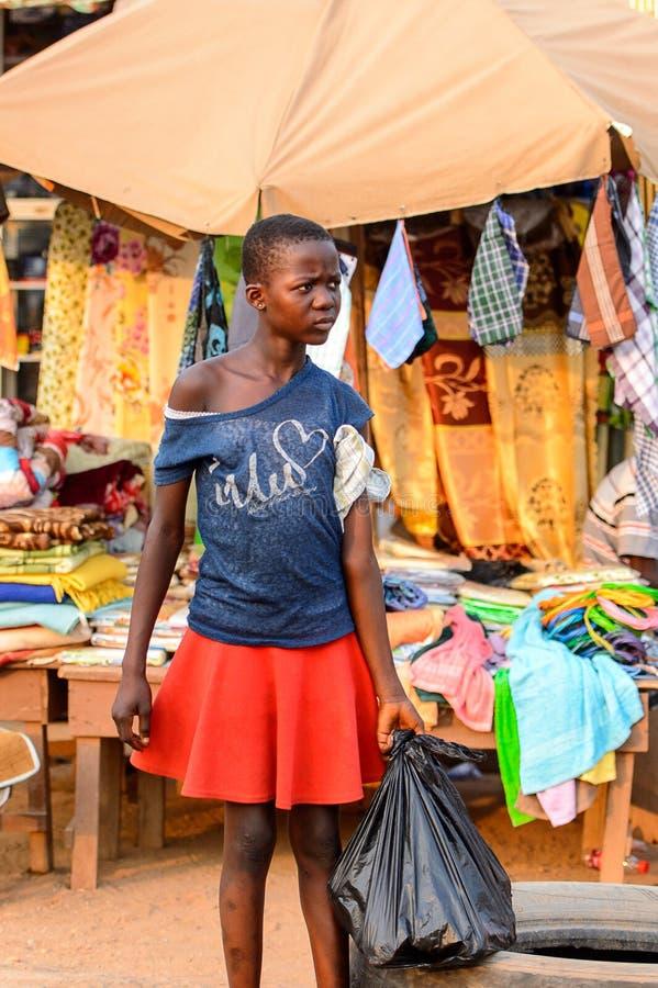 Неопознанная ганская девушка носит полиэтиленовый пакет в местной вилле стоковые фотографии rf