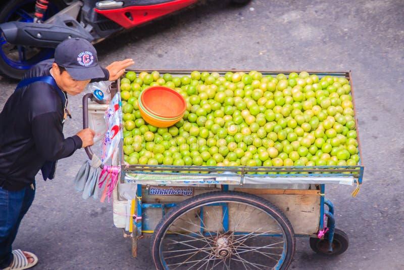 Неопознанная лоточница улицы нажимая тележку на улице для продавать лимон вокруг Бангкока, Таиланда стоковое изображение rf