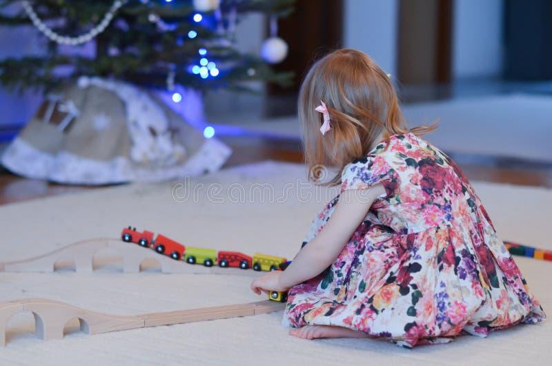 Неопознанная маленькая девочка играя деревянный поезд игрушки стоковые изображения