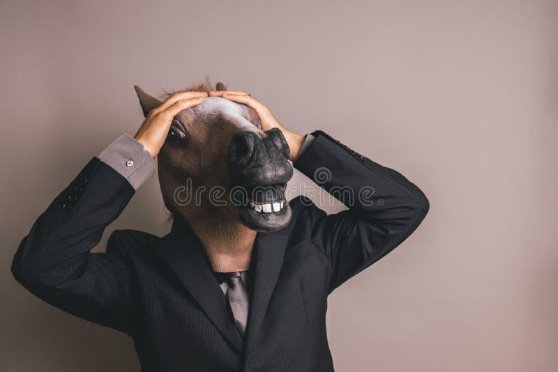 Неопознанная персона при темные серые костюм и связь нося маску лошади с обеими руками на голове стоковые фото