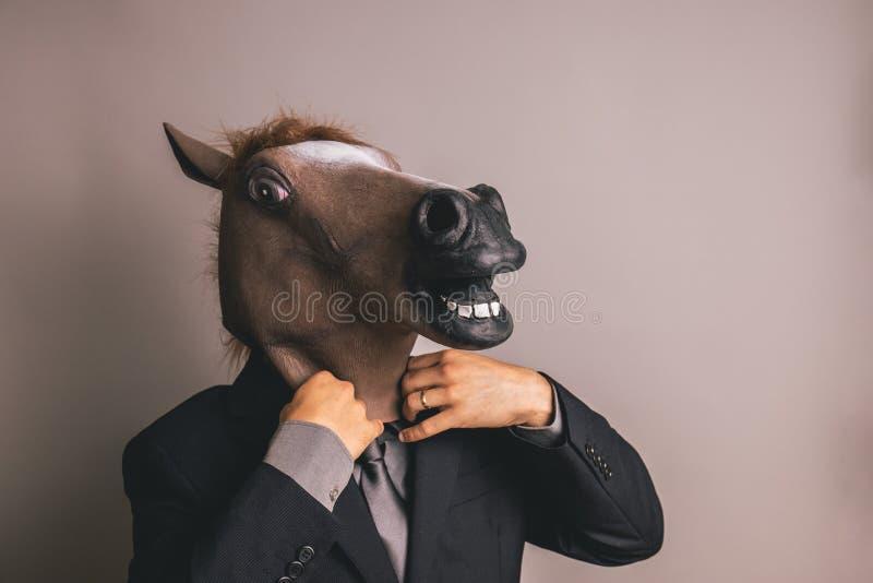 Неопознанная персона с темным серым костюмом и связь нося лошадь маскируют регулировать связь стоковая фотография