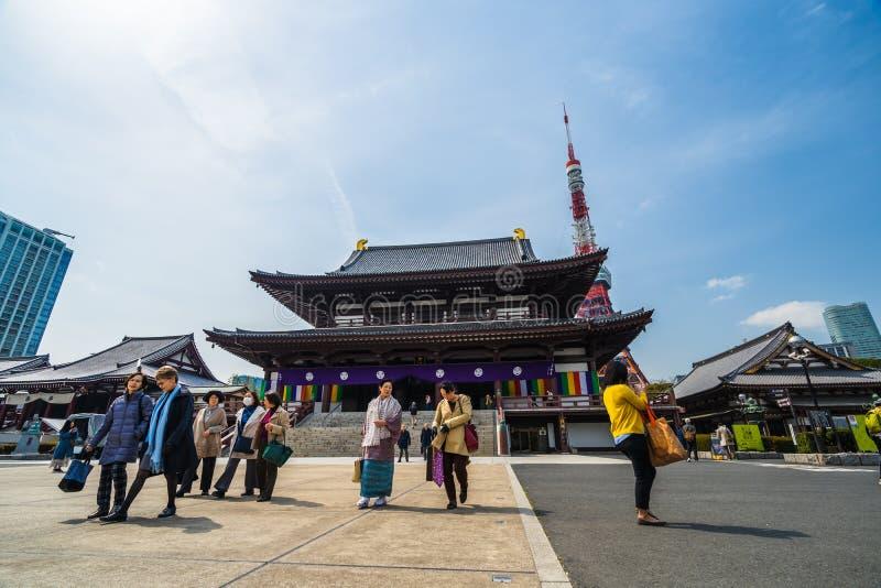 Неопознанное посещение туристов в старом виске Zojoji с предпосылкой башни Токио, этим известное место в Токио, Япония стоковое фото rf