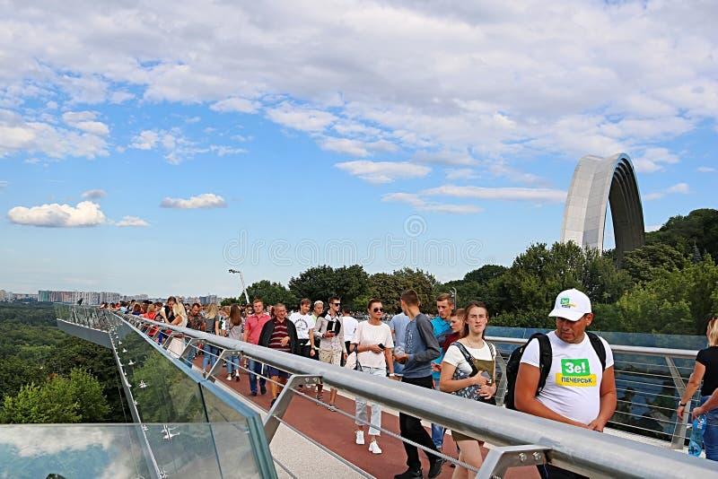 Неопознанные люди идут и ослабляют вдоль моста пешеход-велосипеда над спуском Vladimirsky в выходные дни в Киев, Украину стоковое изображение
