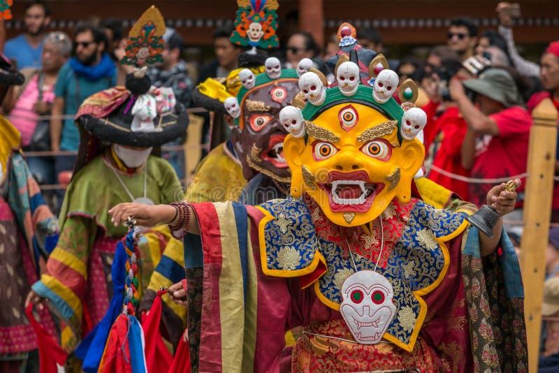 Неопознанные монахи в маске выполняя религиозный замаскированный и костюмированный танец тайны тибетского буддизма стоковое фото