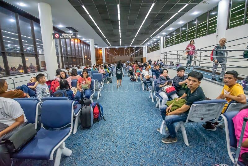 Неопознанные путешественники ждать полет в аэропорте Дон Mueang, Бангкоке стоковые изображения