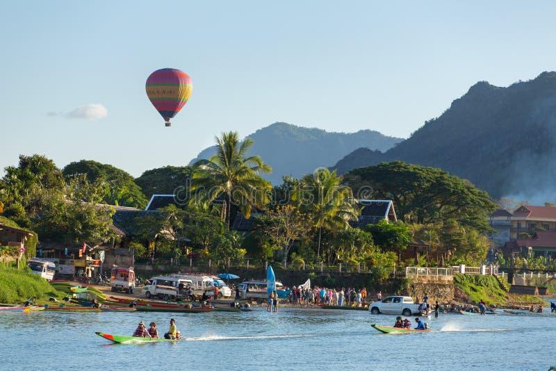 Неопознанные туристы едут быстроходные катера в деревне Vang Vieng стоковое фото rf