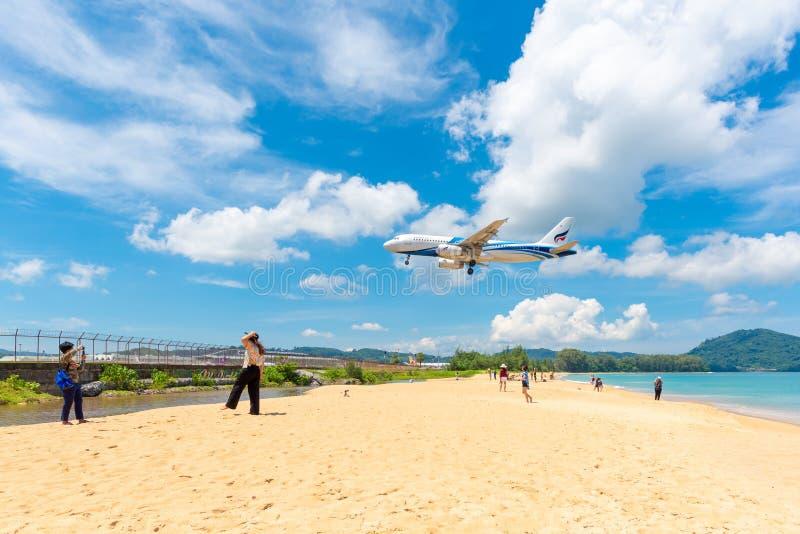 Неопознанные туристы на Mai Khao приставают к берегу с посадкой коммерческого самолета на международном аэропорте Пхукета стоковые фото