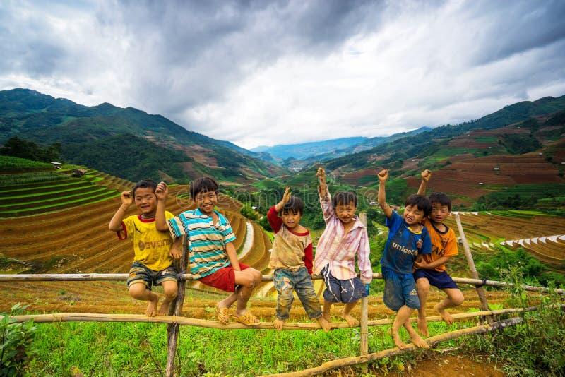 Неопознанные этнические дети ослабляя на горе когда его родители будут работать на террасах стоковое фото