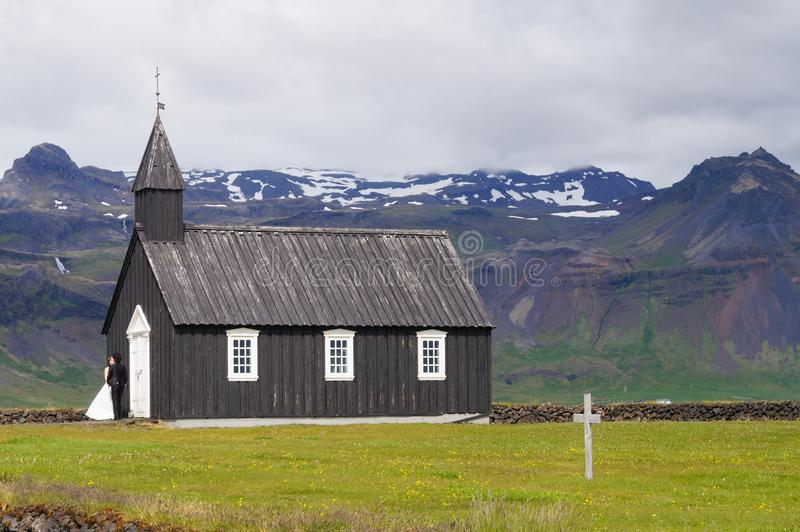 Неопознанный жених и невеста стоя перед известной черной церковью в Budir, Исландии стоковая фотография rf