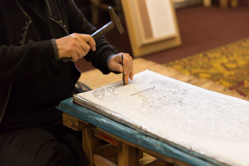 неопознанный молоток пользы женщины для того чтобы высечь декоративное искусство на серебре стоковая фотография rf