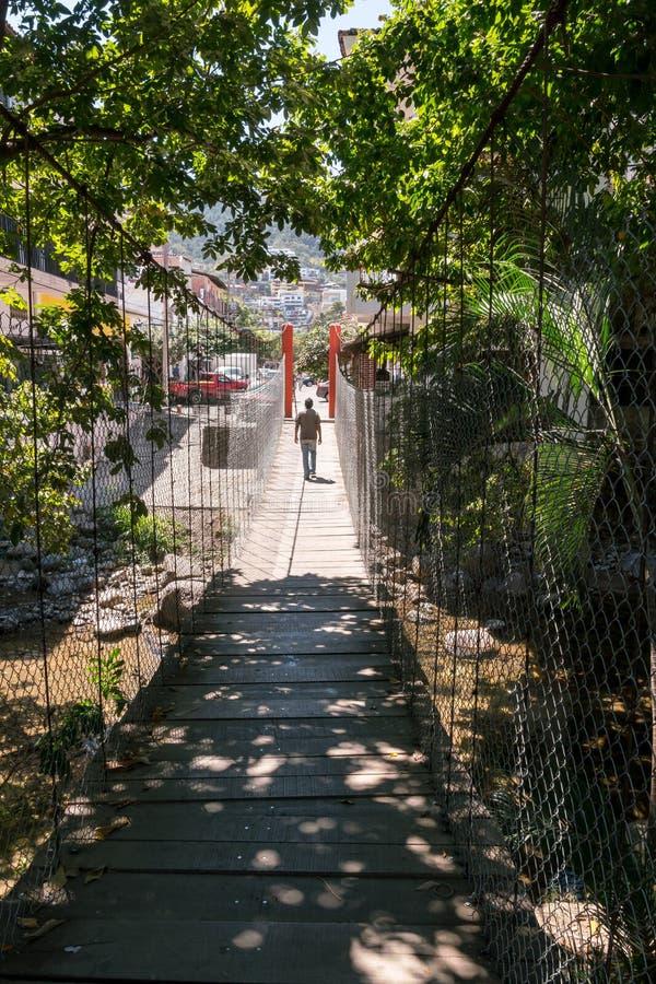 Неопознанный человек идет над висячим мостом от Isla c стоковое фото rf