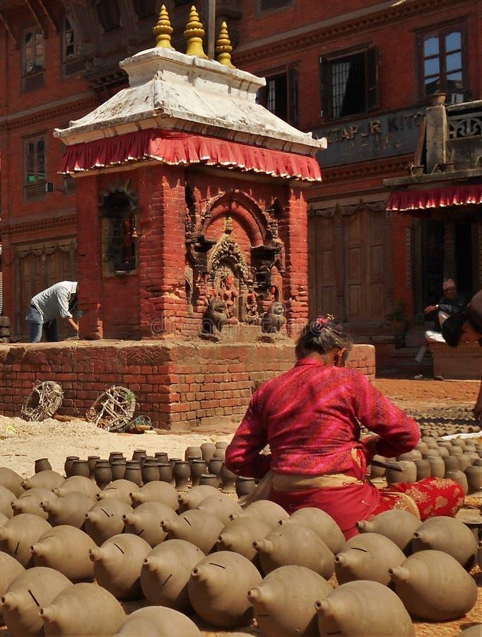 Непальские люди формирующ и сушащ вверх баки керамики в квадрате гончарни стоковое изображение rf