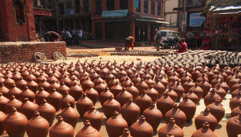 Непальские люди формирующ и сушащ вверх баки керамики в квадрате гончарни стоковое изображение