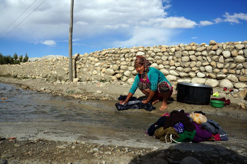 Непал Tsarang Непальская женщина моет одежды в заводи в улице, против фона каменной стены стоковые изображения rf
