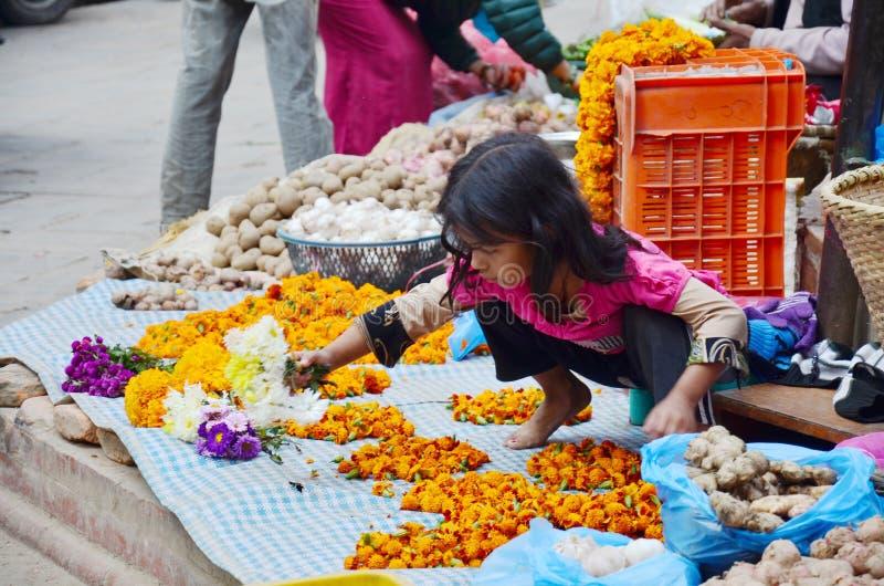 Непальские люди делают гирлянду для продажи на рынке Thamel стоковая фотография rf