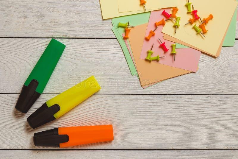 Неподвижный, Pushpins на стикерах, красочных отметках, Highlighters на белой деревянной предпосылке Концепция планированиe бизнес стоковое изображение