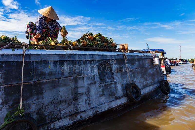Непознаваемая женщина нося традиционную въетнамскую шляпу сортируя ананасы на крыше шлюпки в перепаде Меконга, Вьетнама стоковое фото rf