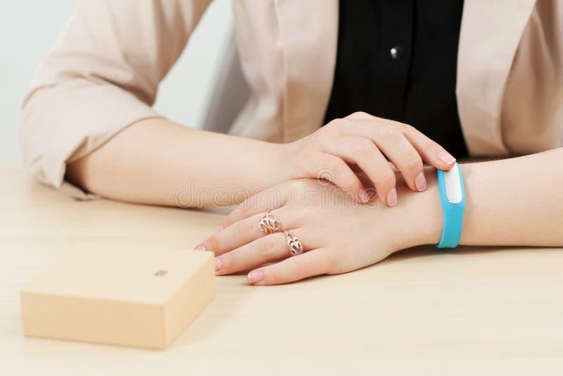 Непознаваемая женщина пробует дальше голубой браслет фитнеса стоковая фотография rf