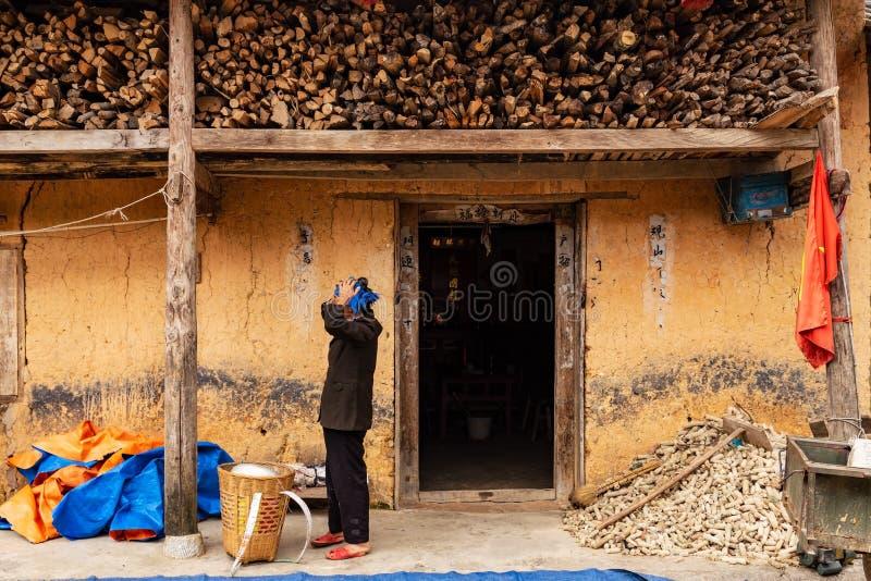 Непознаваемая женщина hmong регулируя ее главный шарф перед традиционным зданием hmong в провинции Ha Giang, Вьетнаме стоковые изображения rf