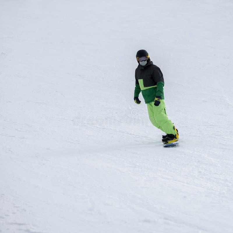 Непознаваемое катание на лыжах snowboarder в ярком костюме, защитной маске стекел на наклоне Спорт зимы, сноуборд, отдых стоковое изображение rf