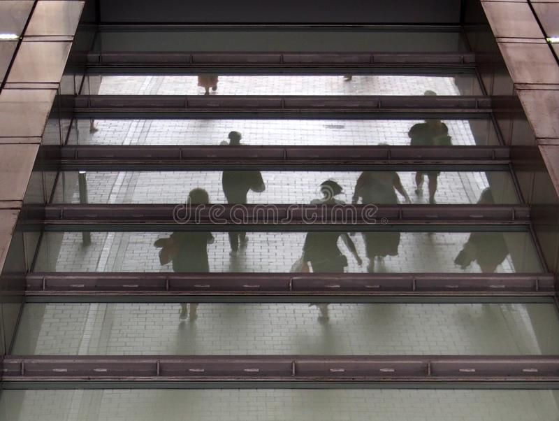 Непознаваемые запачканные люди идя через пешеходную зону отраженную в стеклянном окне здания над городским конспектом стоковые фото
