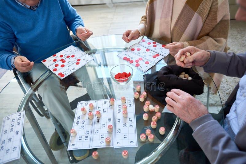 Непознаваемые старшие люди играя Lotto стоковые изображения rf