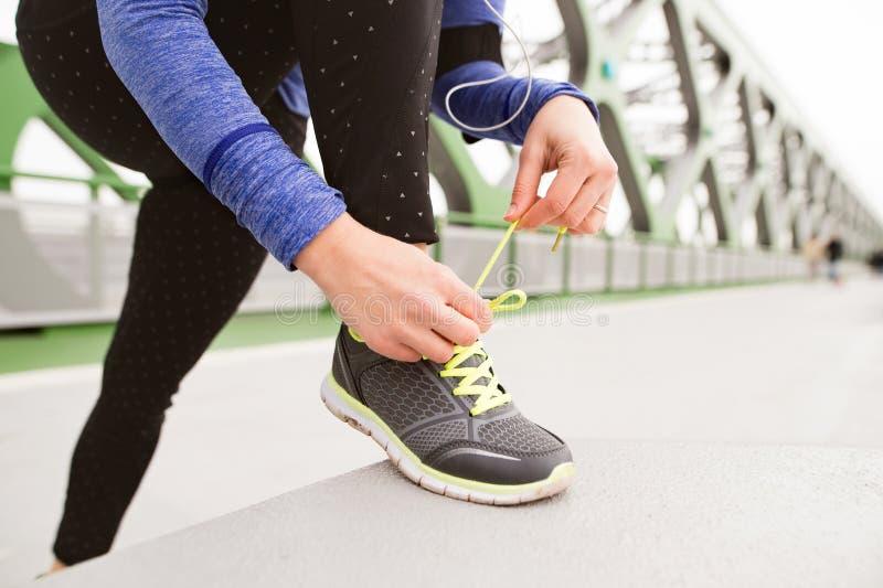 Непознаваемый бегун в городе связывая шнурки на стальном bridg стоковое фото