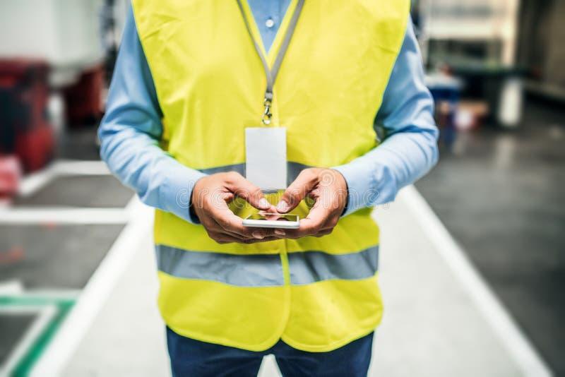 Непознаваемый промышленный инженер человека с биркой имени в фабрике, используя smartphone стоковое изображение rf