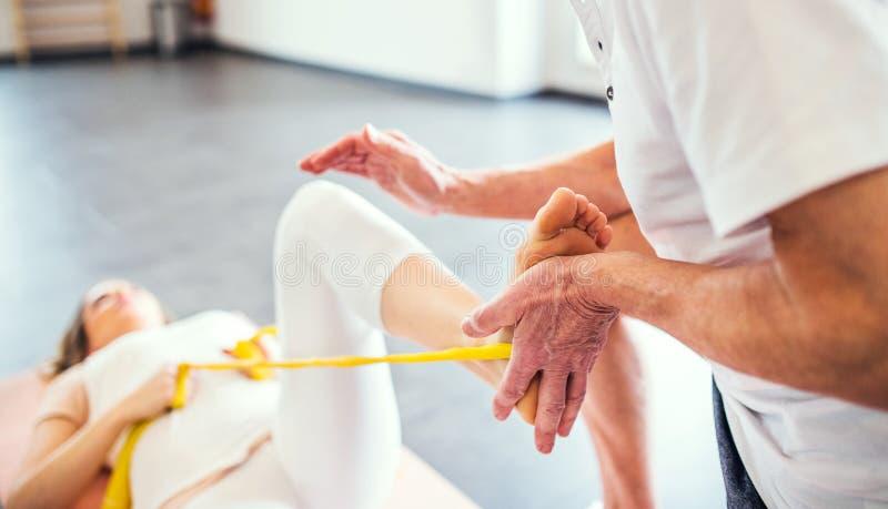 Непознаваемый старший физиотерапевт работая с женским пациентом стоковая фотография rf