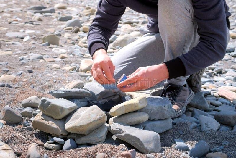 Непознаваемый человек воспламеняет угли в огне со спичками на меднике камней стоковое изображение