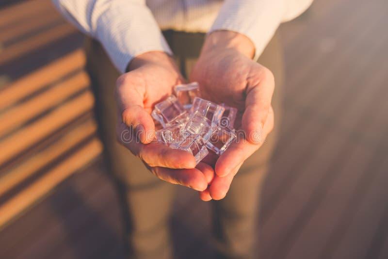 Непознаваемый человек держа кубы льда на заходе солнца стоковые фотографии rf