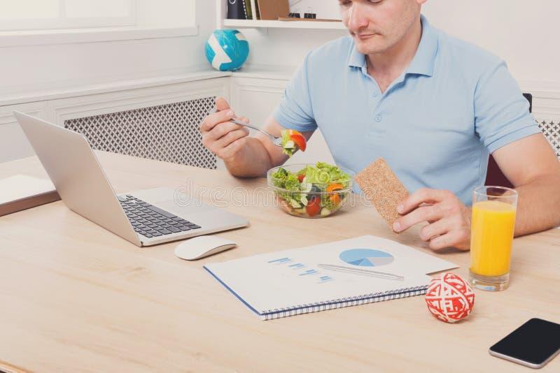Непознаваемый человек имеет здоровый бизнес-ланч в современном офисе i стоковое фото rf