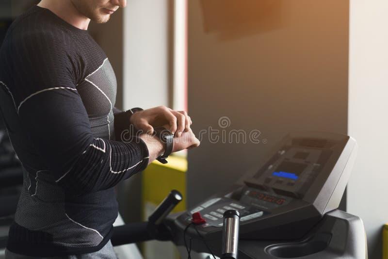 Непознаваемый человек используя отслежыватель фитнеса в спортзале стоковые изображения rf