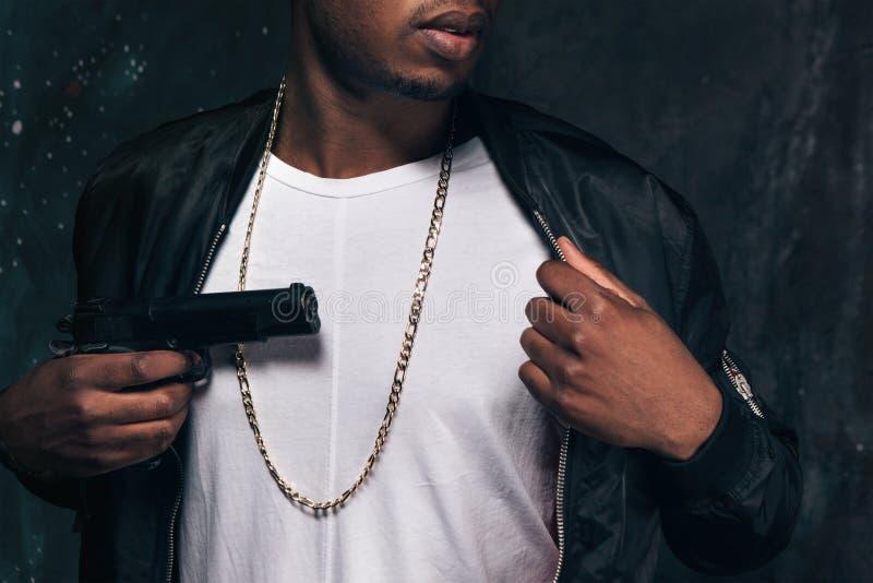 Непознаваемый чернокожий человек угрожает с оружием стоковое изображение