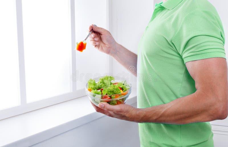 Непознаваемый человек имеет здоровый обед, есть салат овоща диеты стоковое изображение