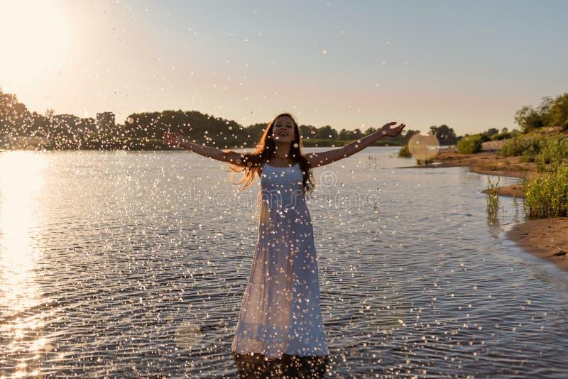 Неполовозрелая маленькая девочка в белом влажном платье стоит в реке и брызгает капельки воды вверх в лучах восходящего солнца стоковое фото rf
