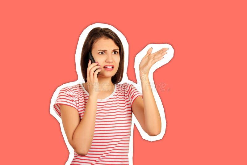 Непонимание и дальний звонок, которые девушка говорит по мобильному телефону, вызывает много вопросов эмоциональная девушка стиль стоковые фото
