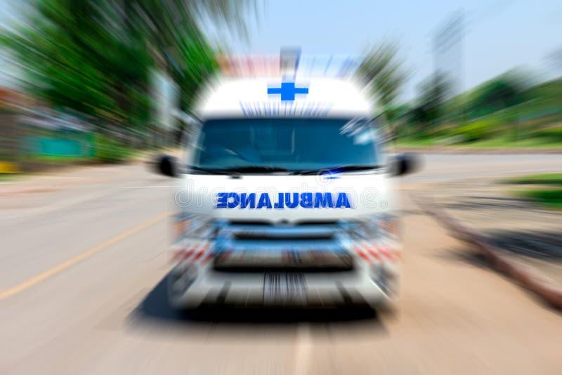 Непредвиденная машина скорой помощи путешествует через улицу города, влияние сигнала прикладное для драматического влияния, нерез стоковое изображение