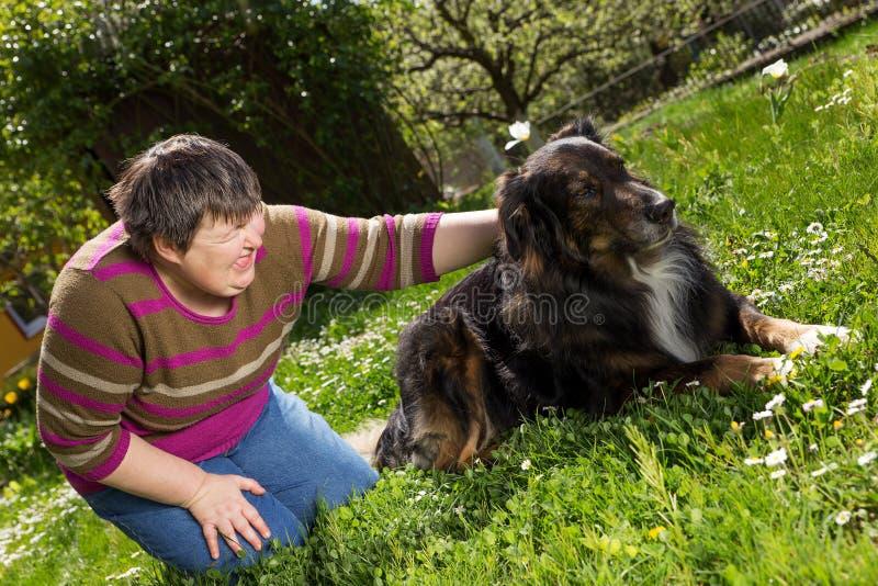 Неработающая женщина на лужайке с собакой стоковые фотографии rf