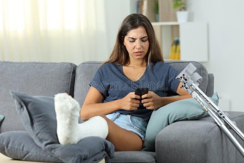 Неработающее послание девушки с телефоном дома стоковая фотография