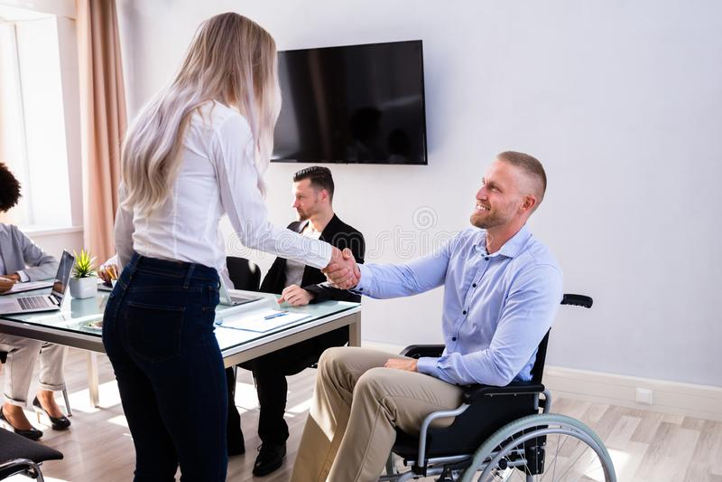 Неработающий бизнесмен тряся руку с его коллегой стоковое изображение rf